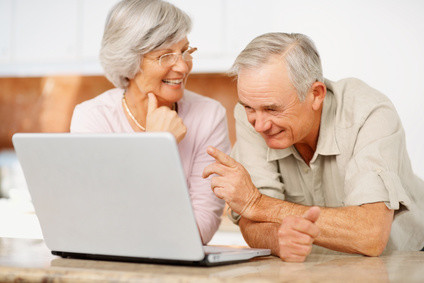 Portrait of a senior man and woman using a computer laptop at home